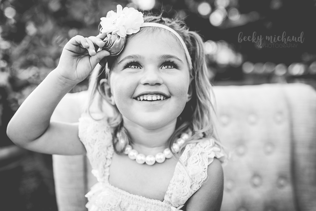 Black and white photo of a little girl posing on a couch during her Fort Collins photography session