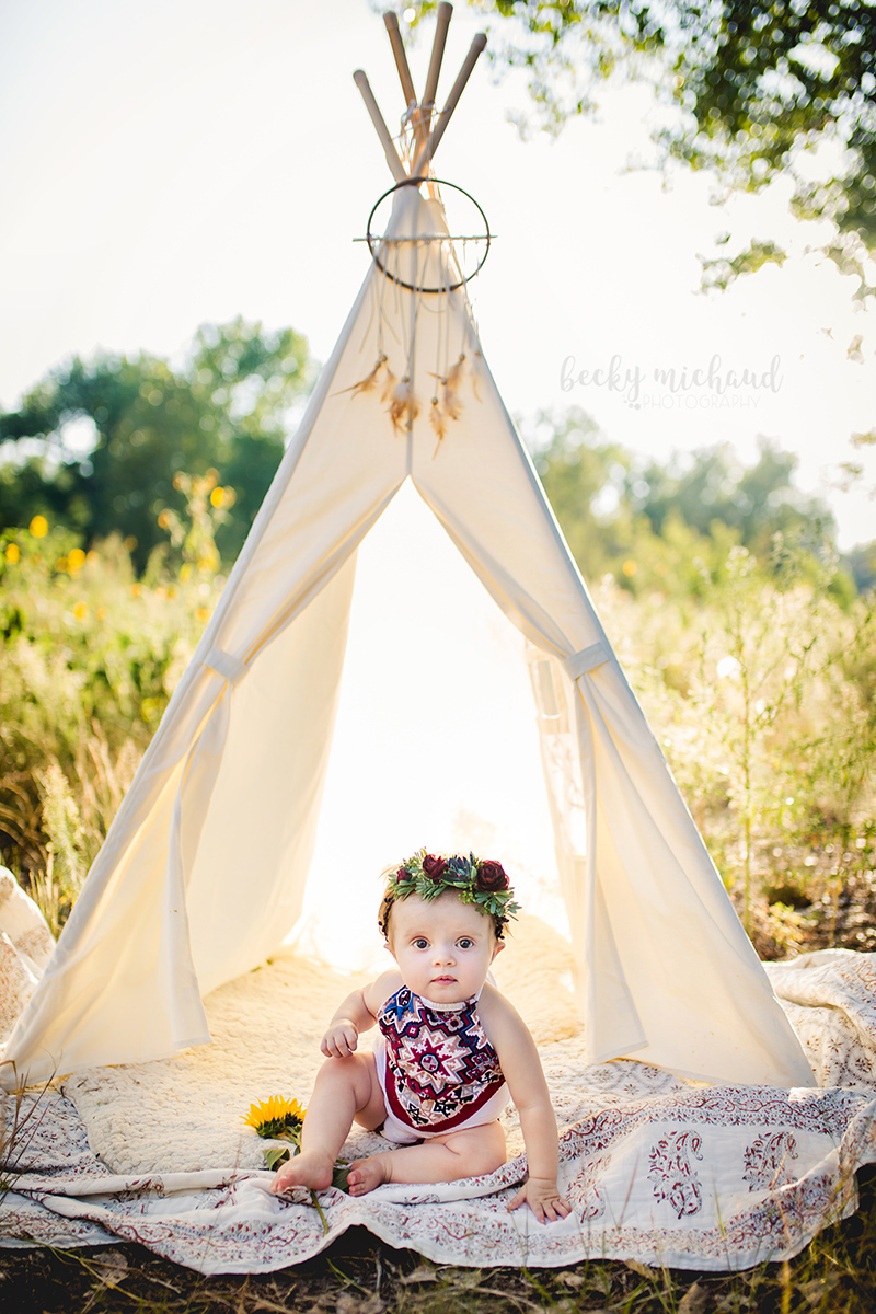 Boho style photo shoot in Fort Collins Colorado of a baby girl in an aztec print romper sitting by a cream colored teepee