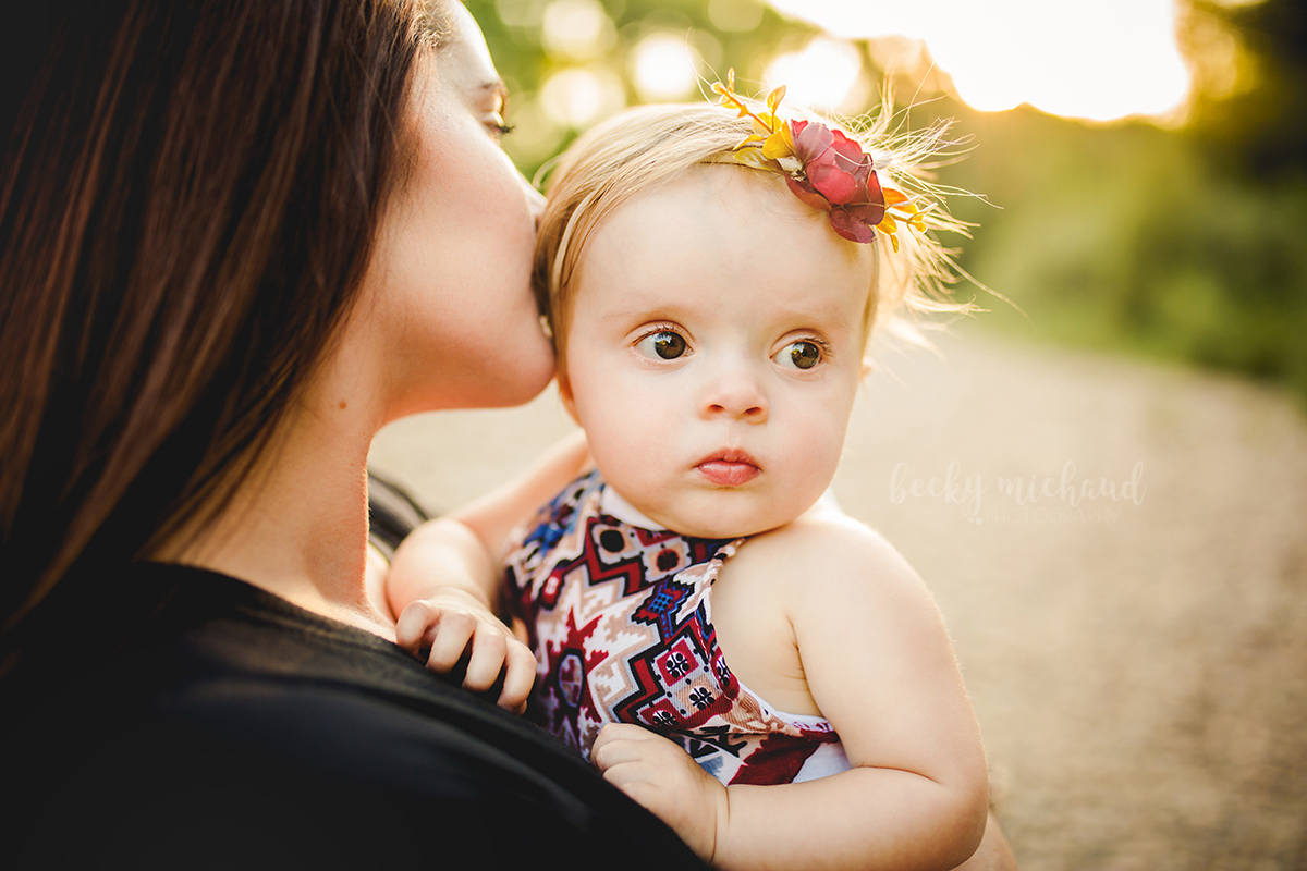 A mom kisses her baby girl's head during their photo shoot at Legacy Park in Fort Collins
