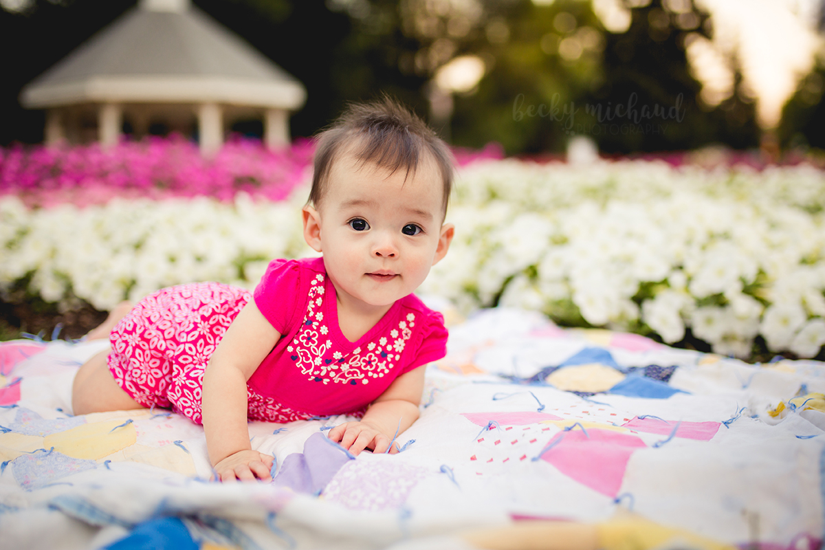 Baby girl plays on a vintage quilt in a flower garden in Fort Collins, CO
