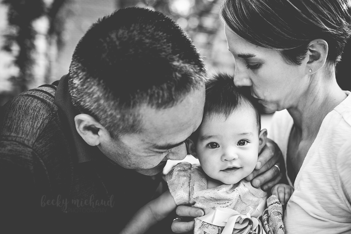 black and white photo of parents kissing their smiling baby girl taken by Becky Michaud, Fort Collins family photographer