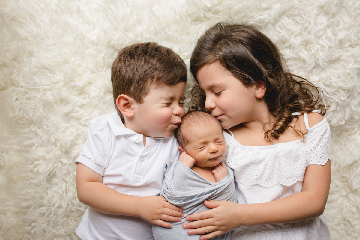 A brother and sister kiss their baby brother during their newborn photo session in their Fort Collins home