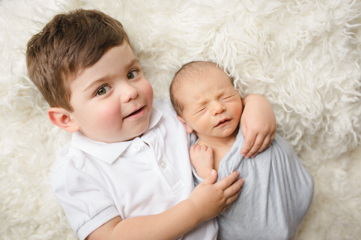 A toddler hugs his new baby brother while lying on a cream fur