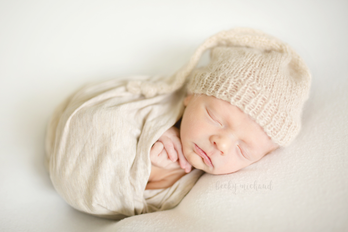 Newborn in a natural hat and wrap sleeps sweetly during his in home photo session