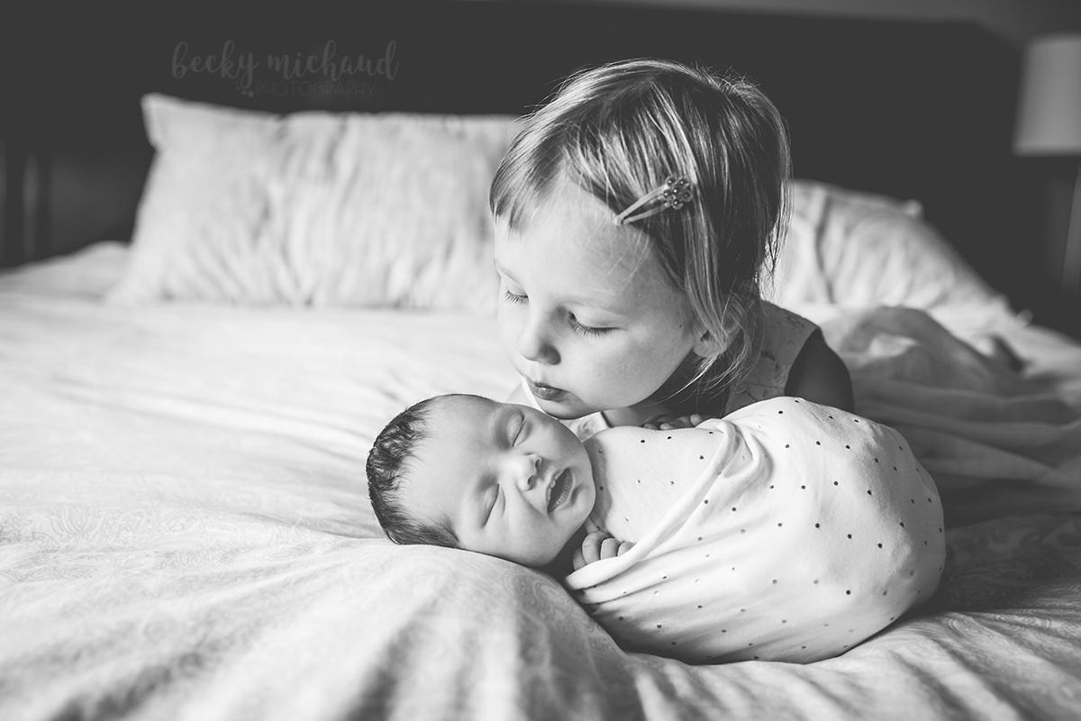A new big sister puckers up to give her baby sister a kiss during their in home newborn session in Fort Collins, CO