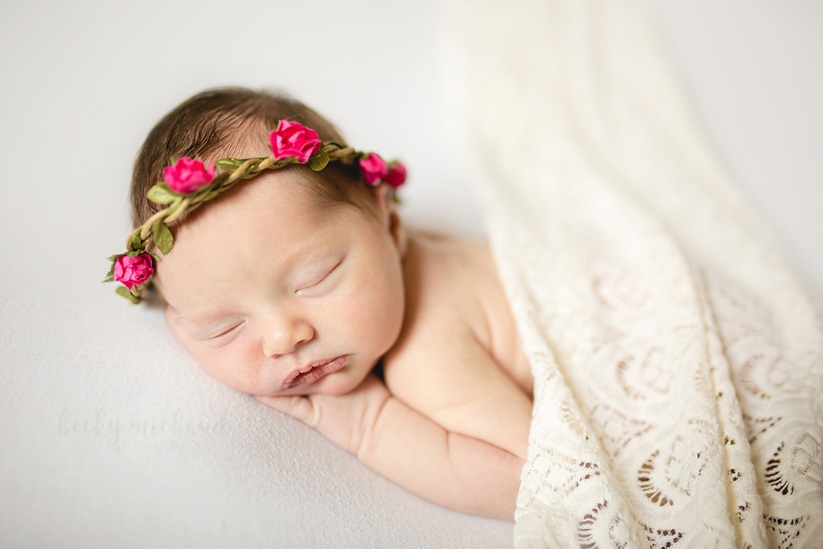 A baby girl wears a pink floral crown and a lace blanket during her Fort Collins newborn photo session