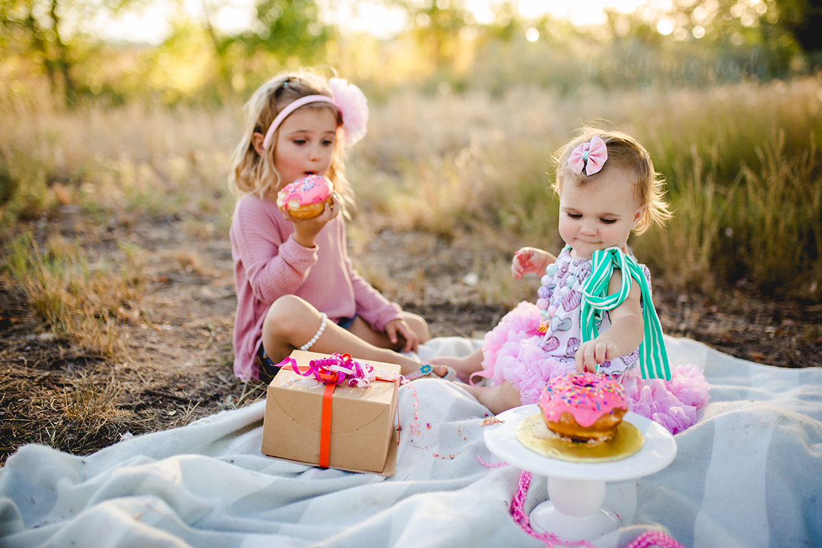 Two sisters share donuts during a cake smash session in Fort Collins, Colorado