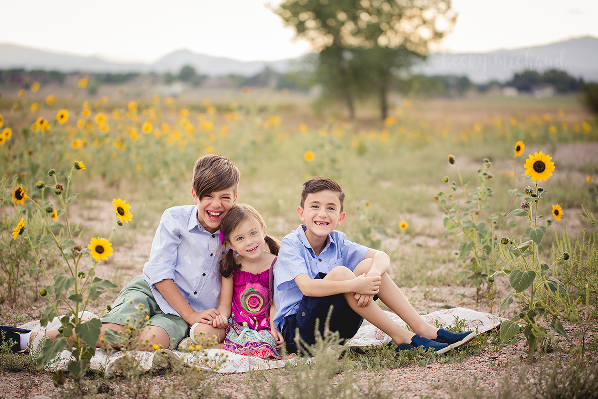 Three siblings sit in a field of sunflowers as the sun sets behind them over the foothills of Fort Collins