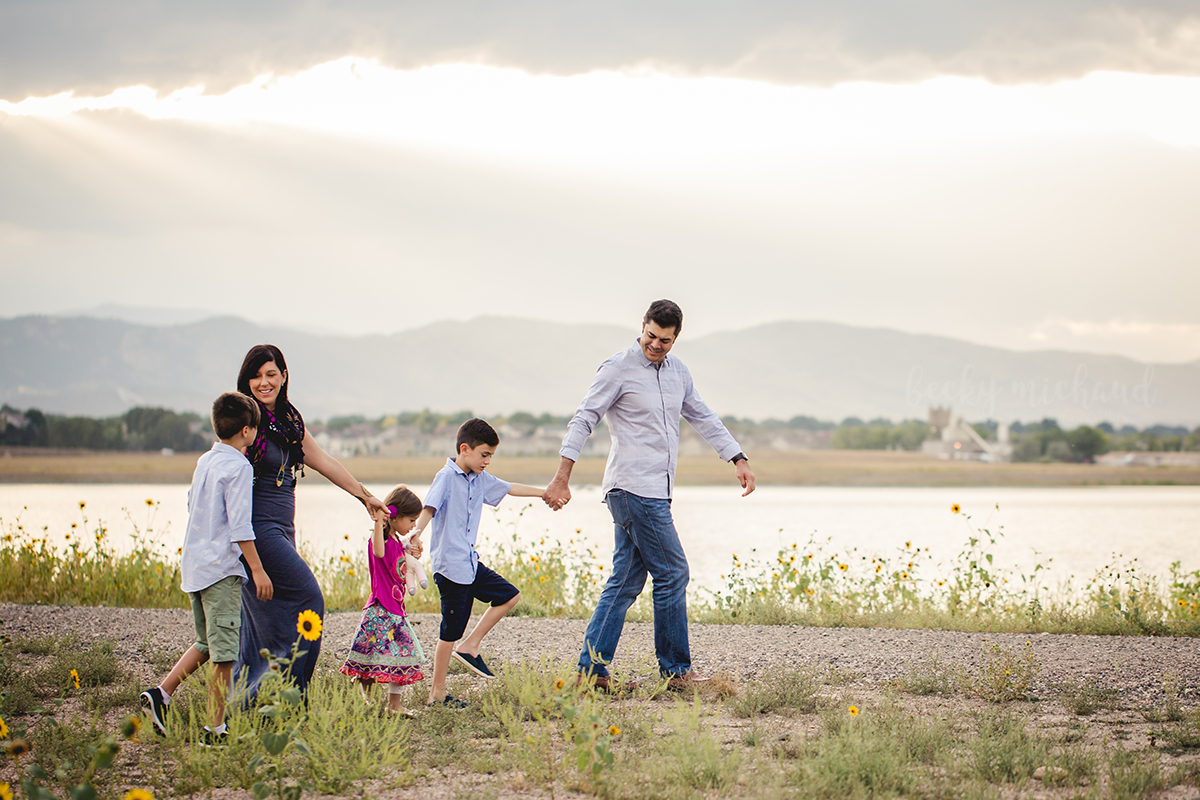 A family walks by a lake during their family photo session in beautiful Fort Collins, Colorado