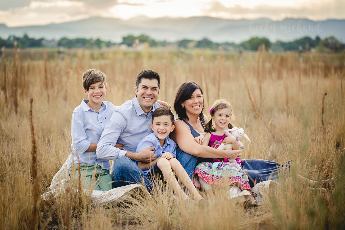 A family poses in a field with the Colorado mountains in the background during their outdoor family photo session