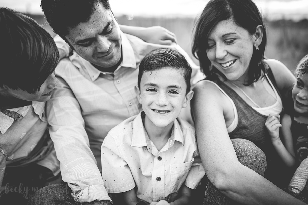 Black and white photo of a boy surrounded by his family taken by Becky Michaud, Fort Collins photographer