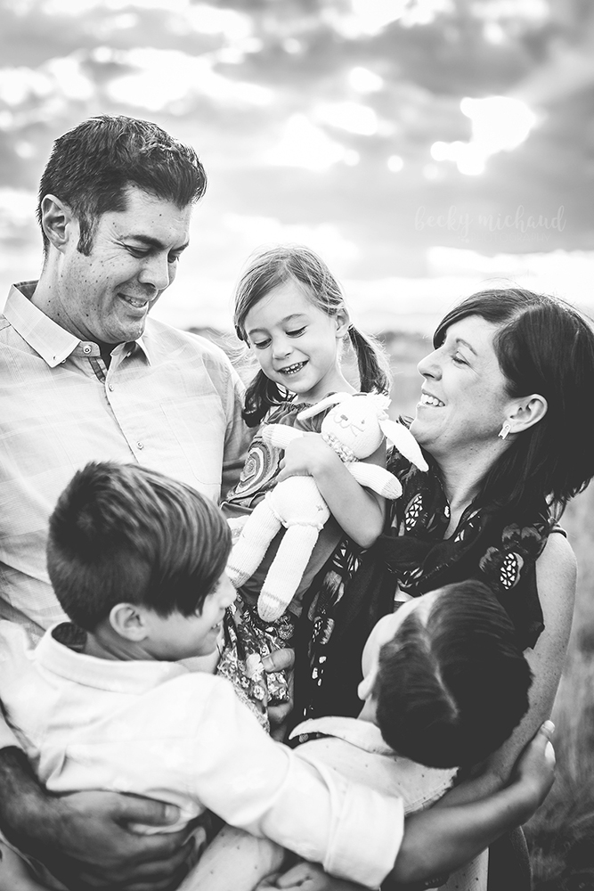 Black and white photo of a family embracing their young daughter as the sun sets behind them in Northern Colorado