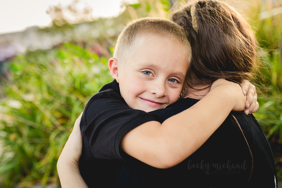 A boy hugs his mom and smiles while taking family photos in Old Town