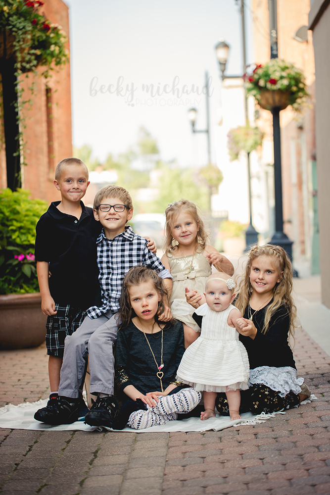6 siblings sit together for their Old Town Fort Collins family portrait session