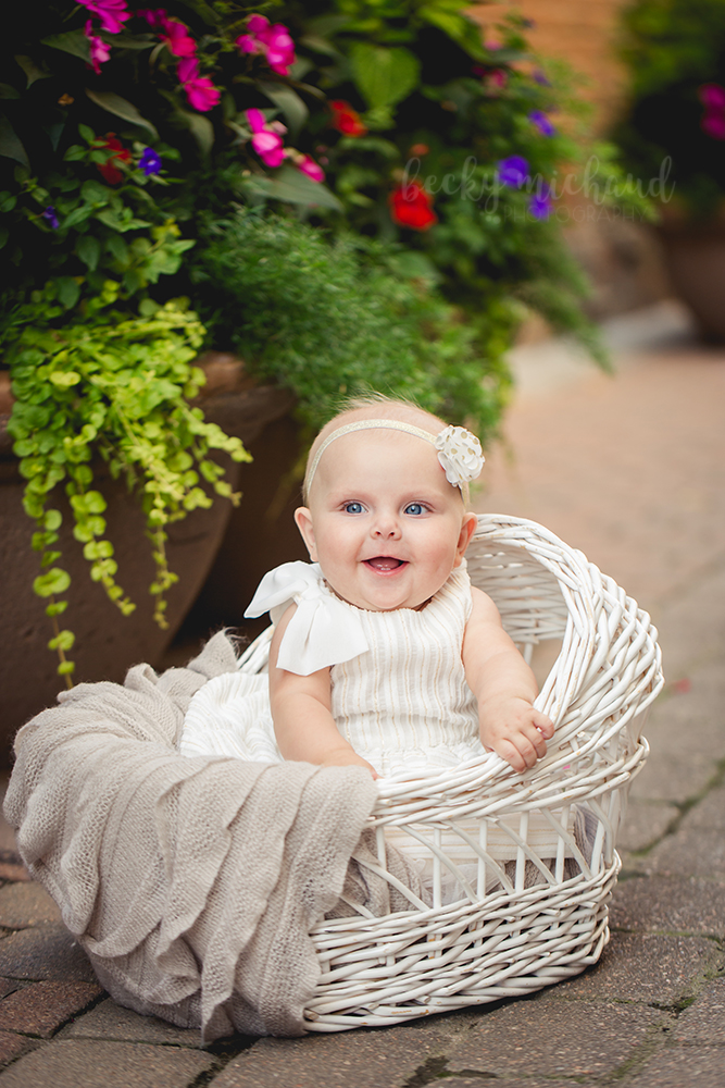 A baby sits in a wicker basket by some beautiful flowers in Old Town Fort Collins