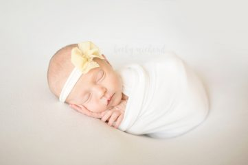 Simple newborn photo of a baby girl in a white wrap with a yellow bow, taken in her Timnath, Colorado home