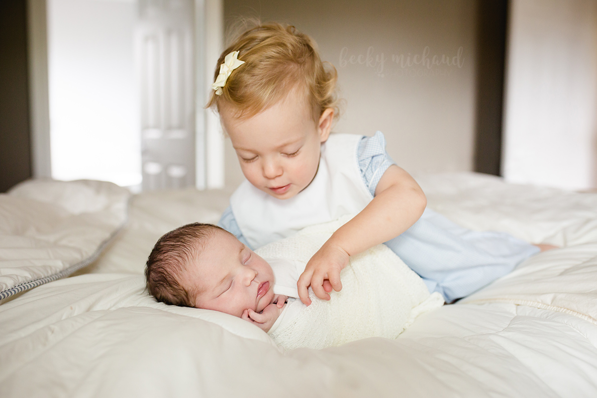 A big sister plays with her newborn sister on a bed during their photo session in their home in Fort Collins
