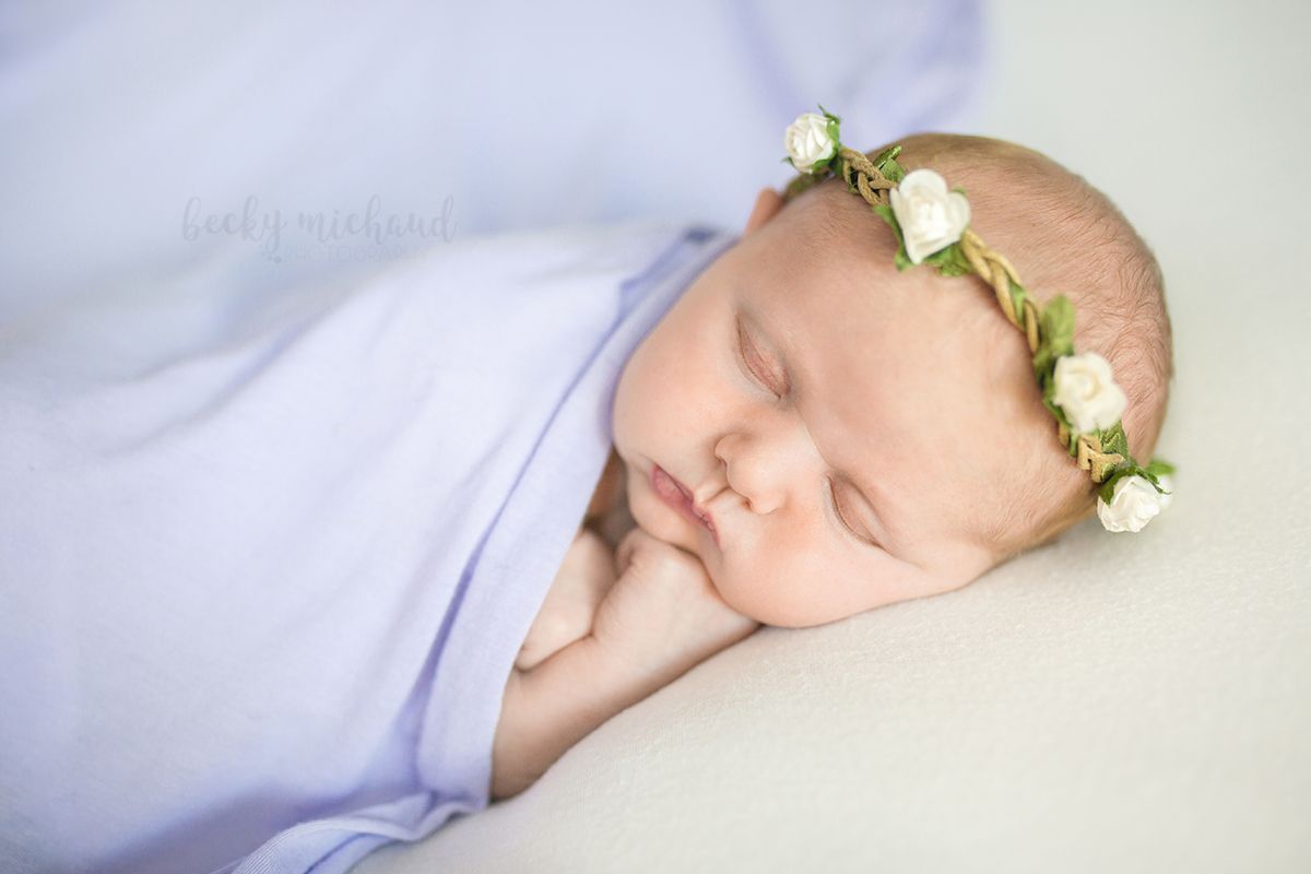 A newborn girl in a purple blanket with a white flower crown