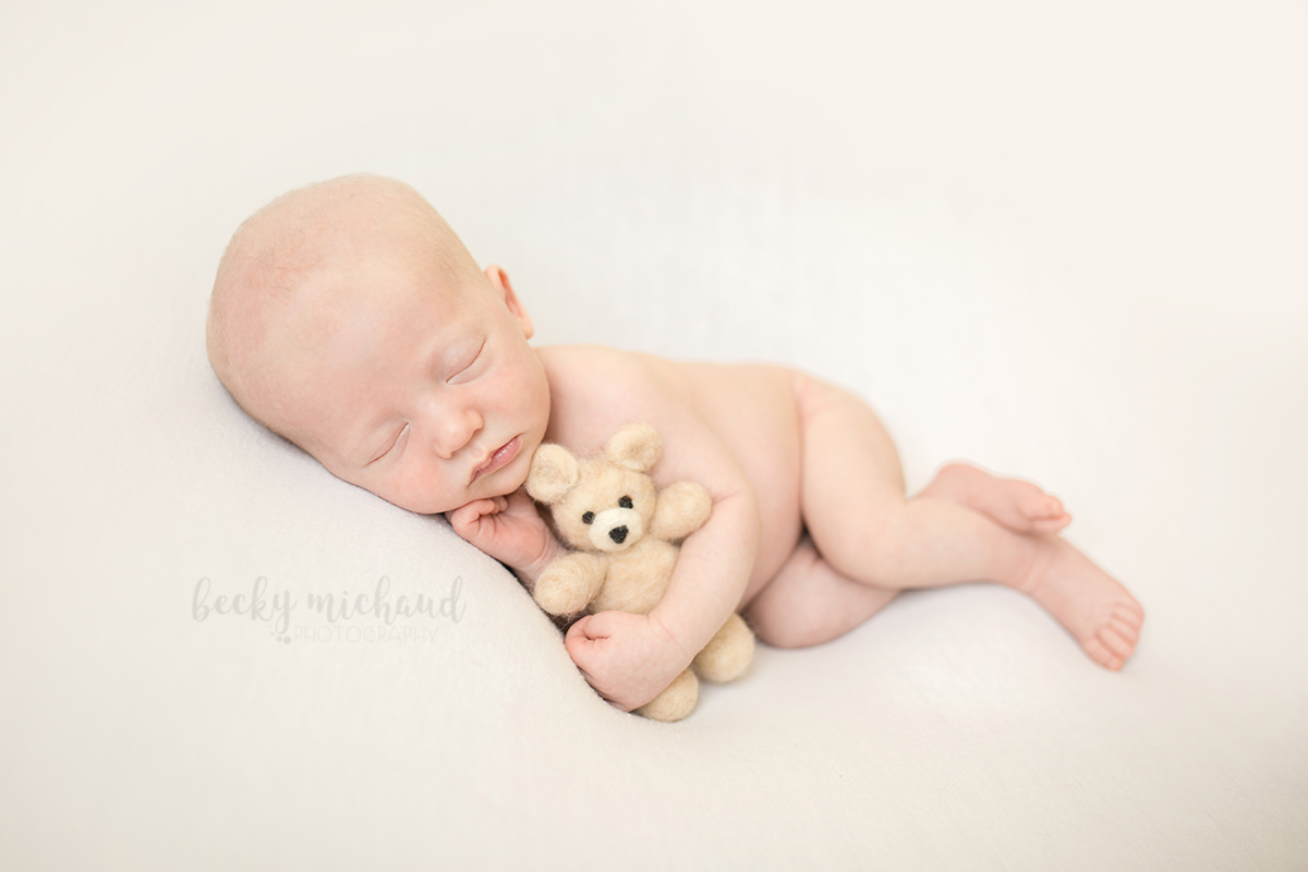A baby boy cuddles with a teddy bear in a simple newborn photo on a white background