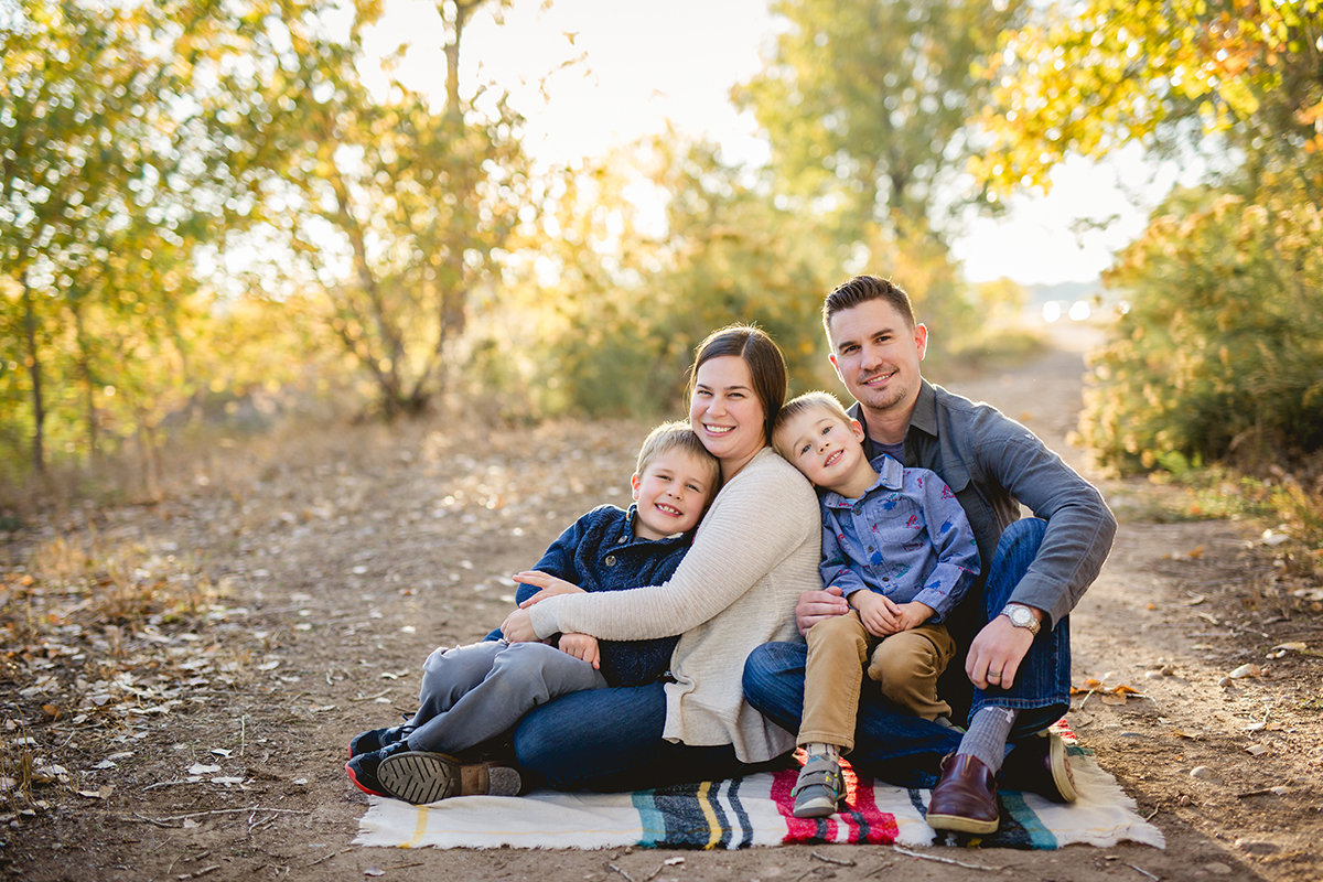 A family poses for their fall photos at Arapahoe Bend Natural Area in beautiful Fort Collins