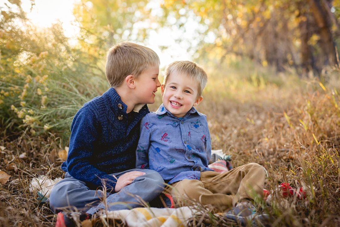 Two brothers share a secret during their Fort Collins family photo session
