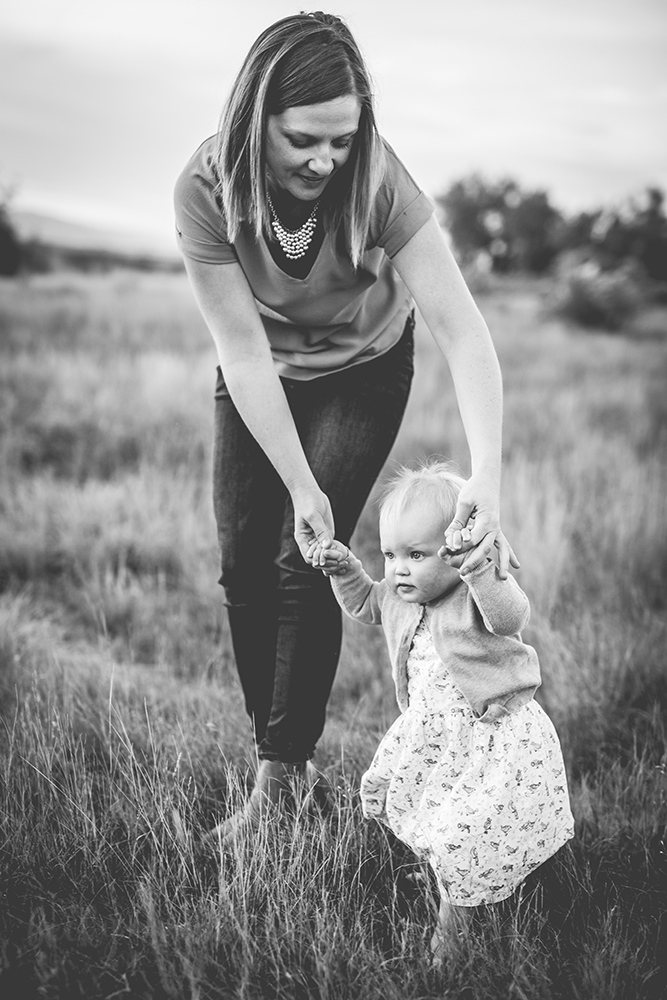 black and white photo of a mom helping her baby walk taken by Becky Michaud, Fort Collins photographer