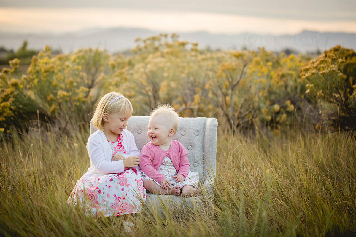 Two sisters in pink laugh together on a little couch in a field at sunset