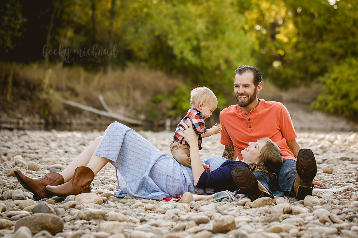 A family plays by the Poudre River during their family photo session in Fort Collins
