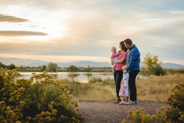 A family of four watches the sunset during their Northern Colorado family photo session