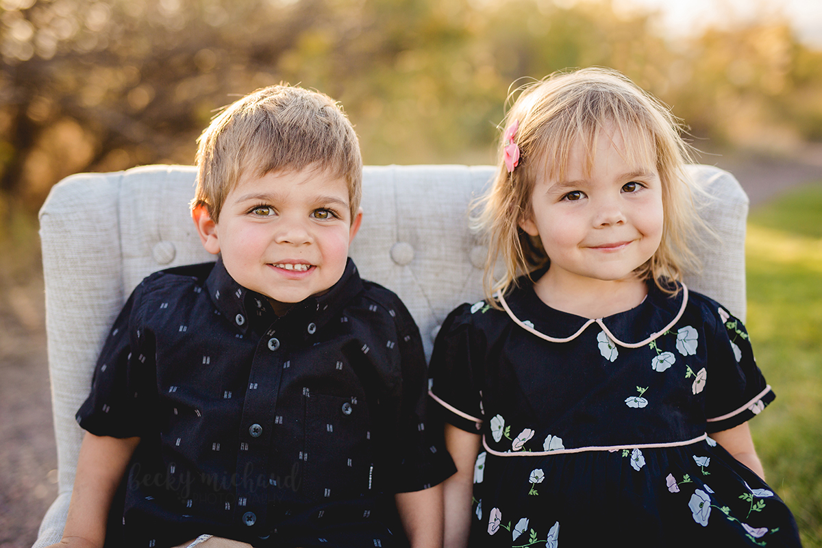 A brother and sister sit on a little couch together during their Loveland, Colorado family photo session