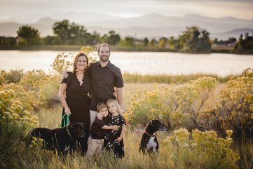 A family and their two dogs pose by a lake in Loveland Colorado with the mountains in the distance
