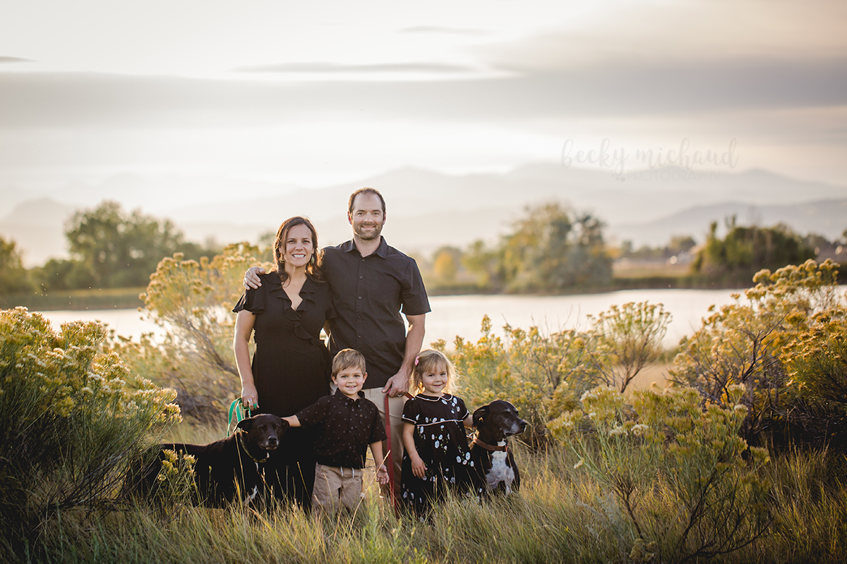 Becky Michaud, Northern Colorado family photographer, captures a family of four in front of a lake and mountain range