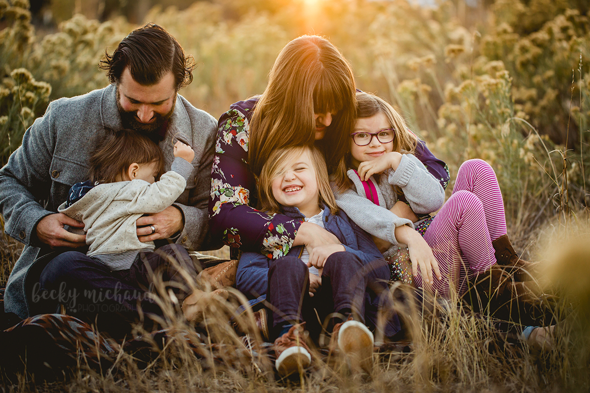 A family laughs together in a field at a Fort Collins Natural Area during their family photo session