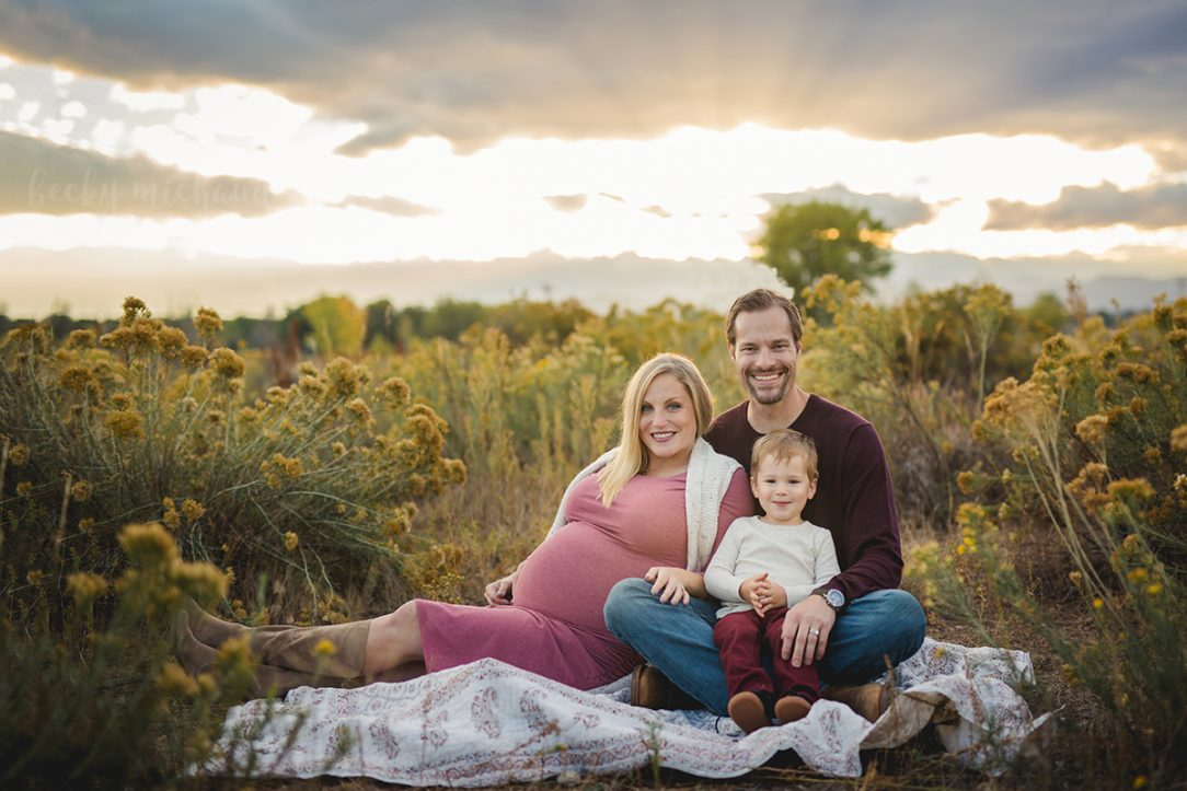 A family of three sits on a blanket with the sun setting behind them during their maternity photo shoot in Fort Collins, Colorado