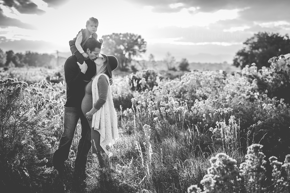 A couple kisses in a field with their son on dad's shoulders during their Fort Collins maternity photo session