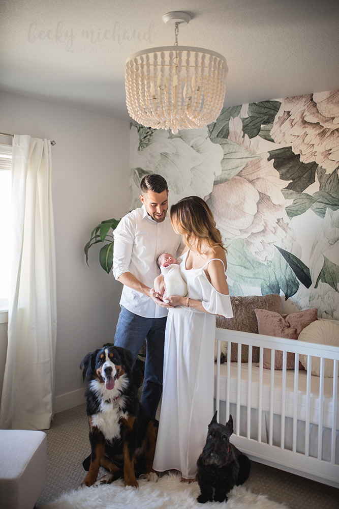 New parents admire their baby girl in her beautiful nursery with their dogs by their side in a photo taken by Becky Michaud, Fort Collins newborn photographer