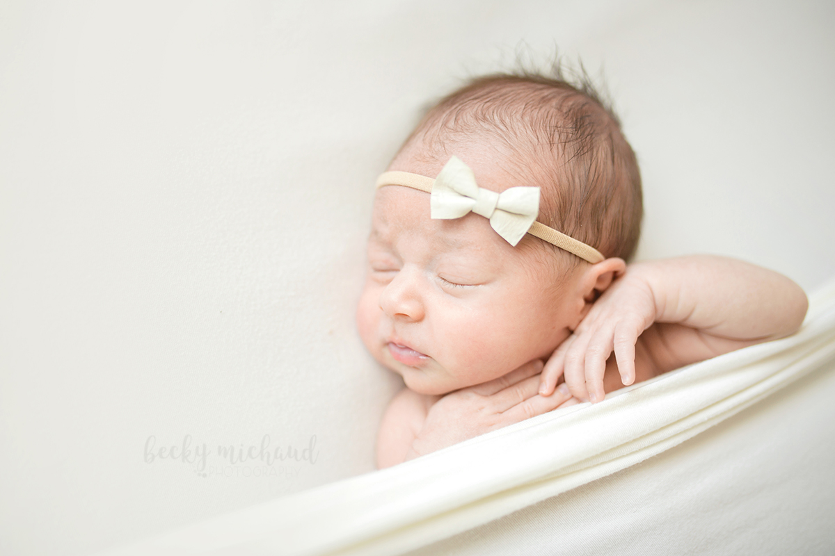 A baby girl sleeps tucked under a white blanket for a photo taken during her newborn session in her Fort Collins home