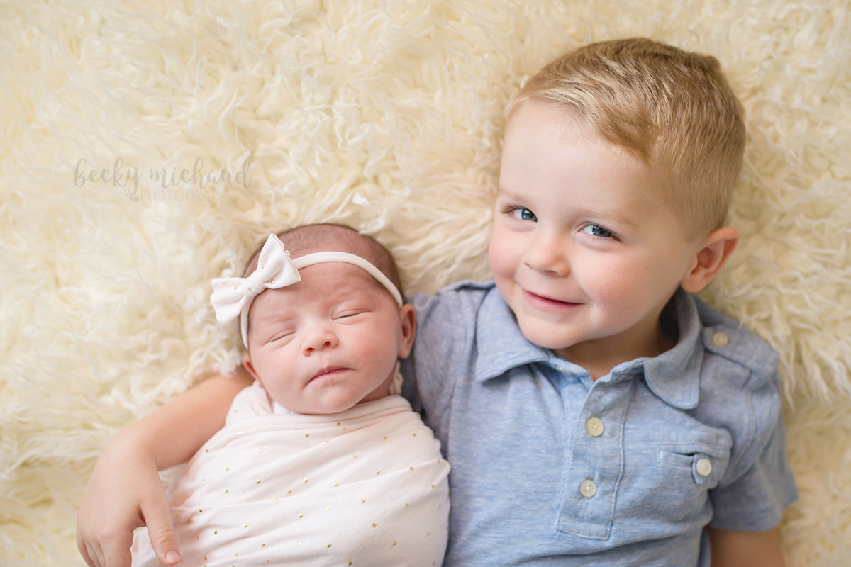 A new big brother holds his baby sister during her in home Fort Collins newborn session