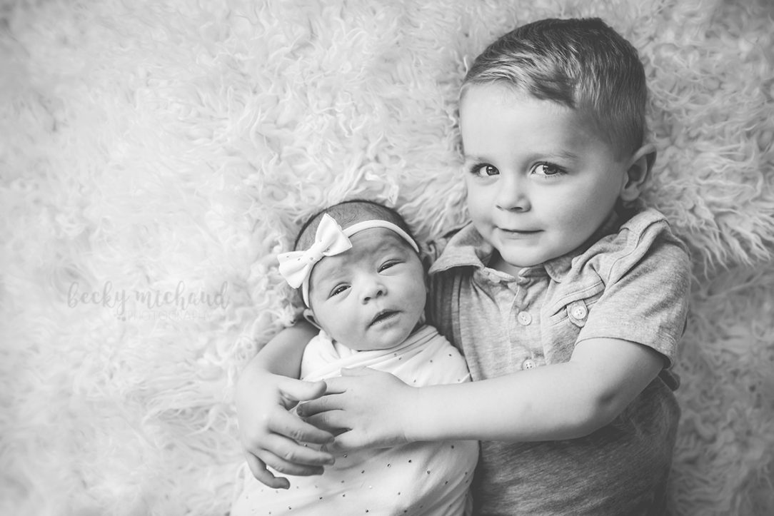 Black and white photo of two siblings posing together on a blanket for newborn photographer Becky Michaud in their Fort Collins home
