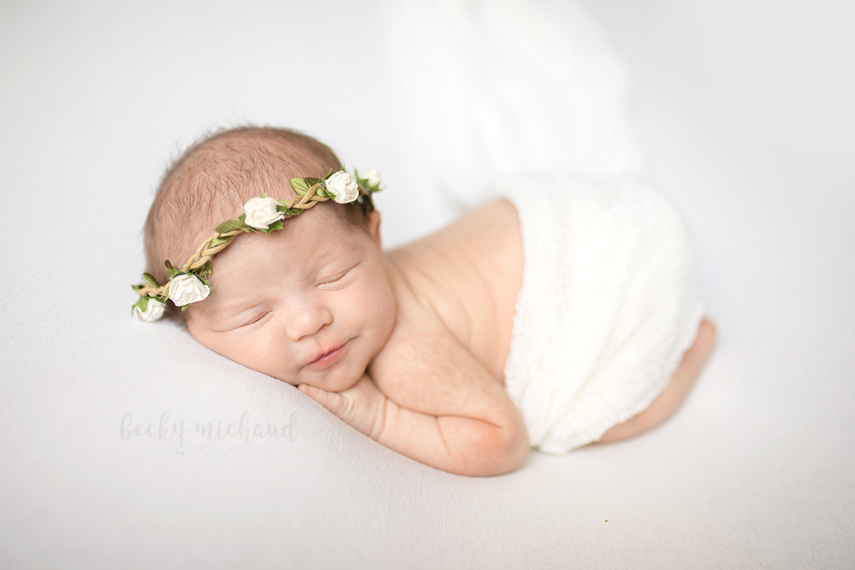 A newborn baby girl wears a flower crown on a white blanket