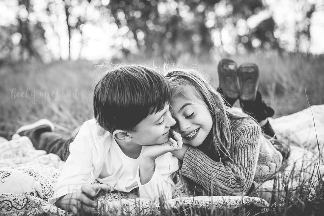 black and white photo of a pair of siblings cuddling together on a blanket during an outdoor family photo session in Northern Colorado