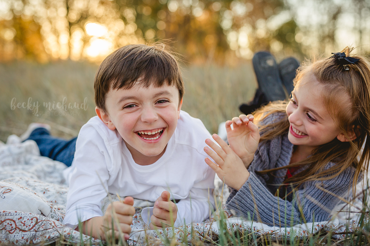 A brother and sister laugh together at Arapahoe Bend Natural Area in Fort Collins, Colorado