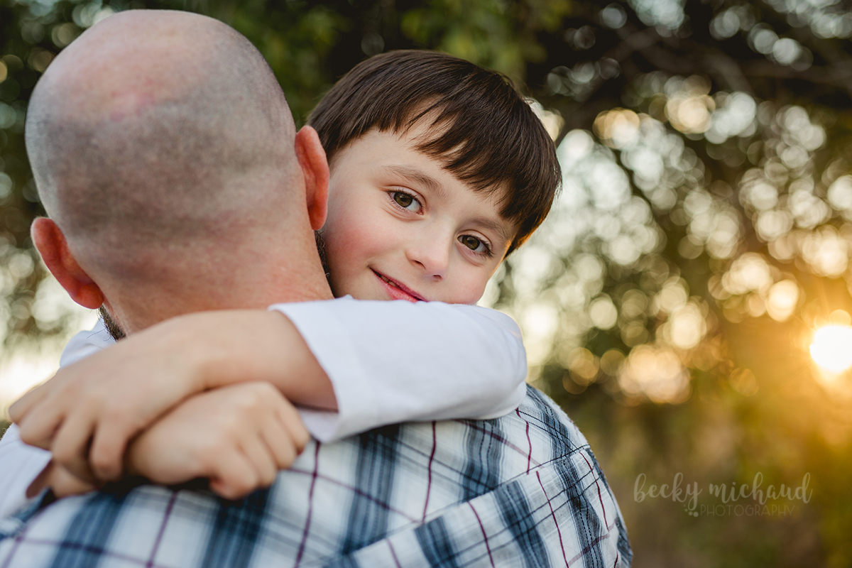 A boy hugs his dad around the neck during their fall family photo session