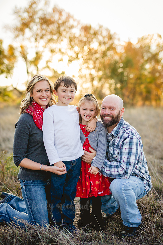 A family of four poses for their fall photos in a field in Fort Collins with the sun setting behind them