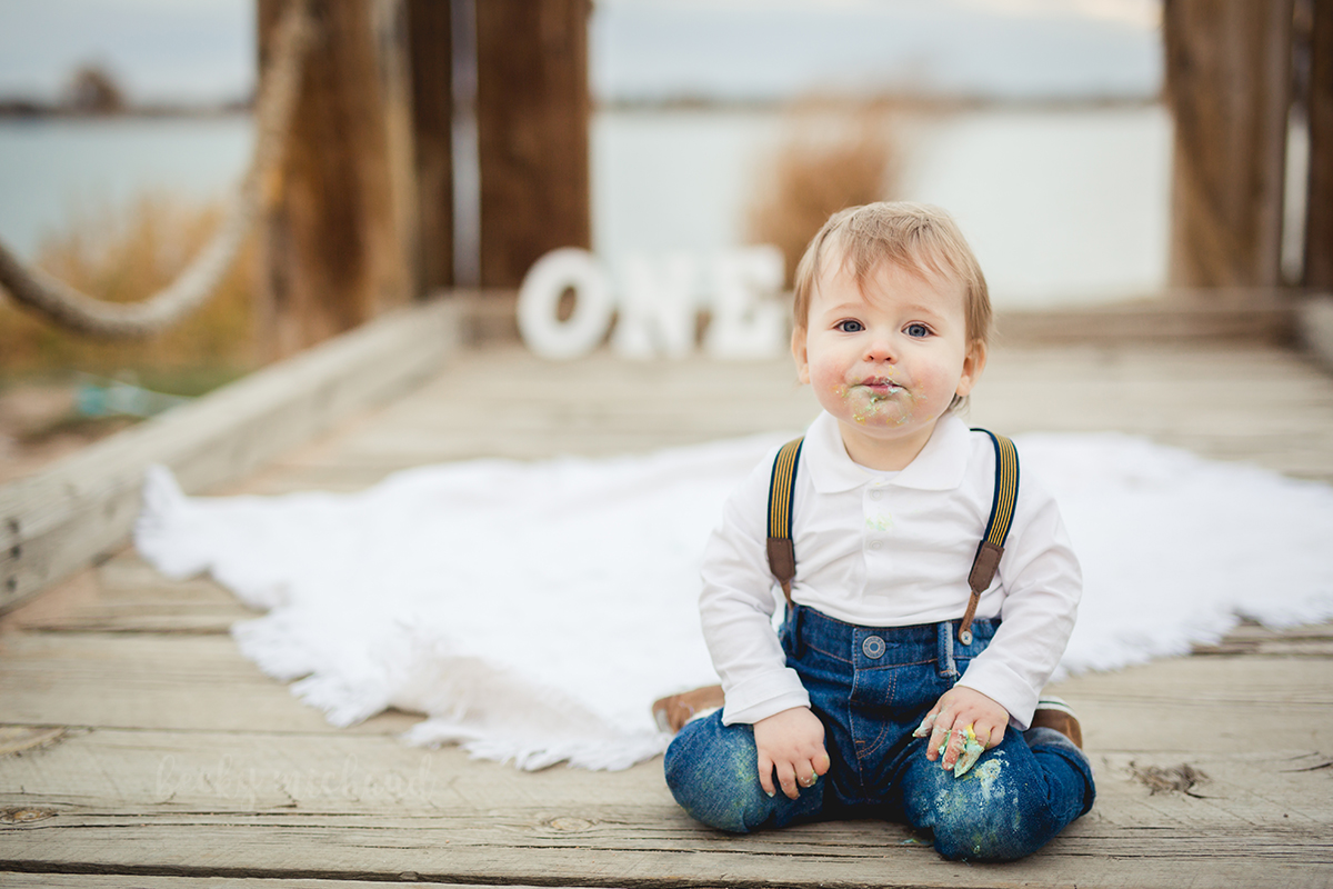 A baby boy takes a break from his cake smash session on the dock of Windsor Lake