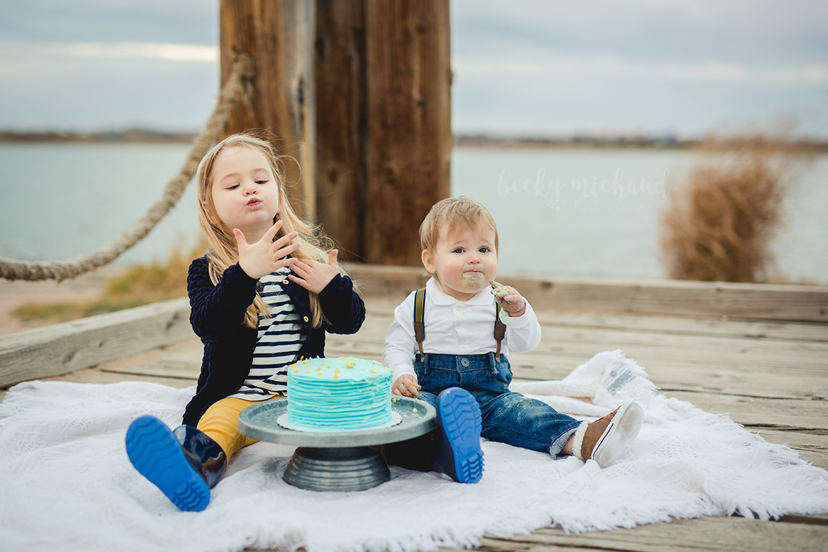 Big sister gets to join in the fun during her brother's cake smash photo shoot in Northern Colorado