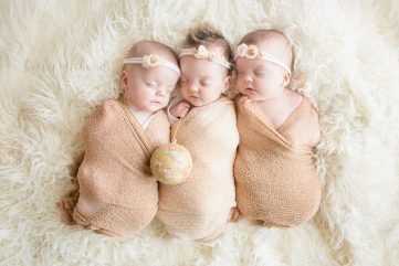 newborn triplet sisters on a neutral background with a Christmas ornament