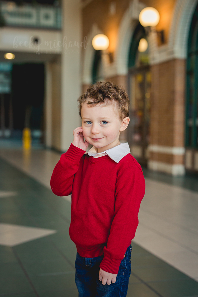 A little boy in a red sweater stands in the Opera Galleria in Old Town during his Fort Collins photography session