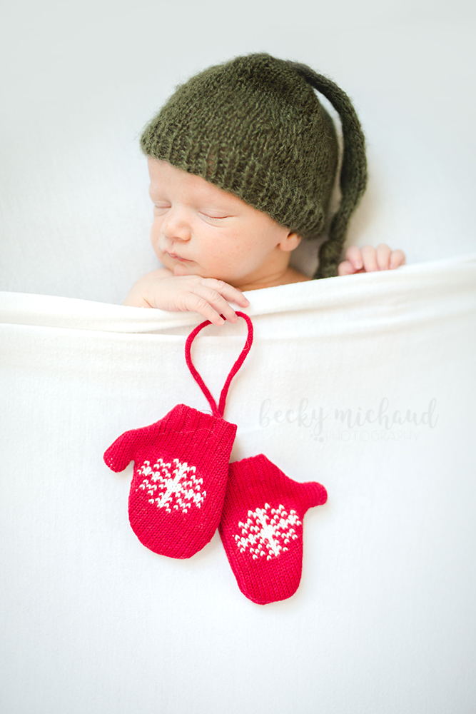 Newborn baby tucked in under a white blanket holding a red pair of mittens in a Christmas newborn photo