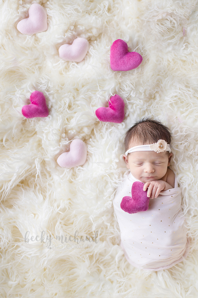 Newborn baby girl with pink hearts in a photo taken by Becky Michaud, Fort Collins photographer